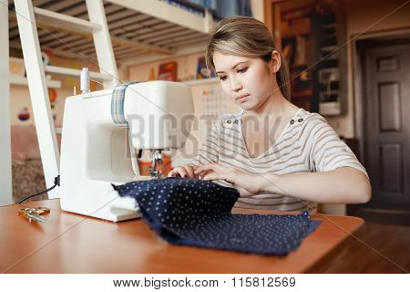 Young woman sewing with sew machine at home while sitting by her working place. Fashion designer car