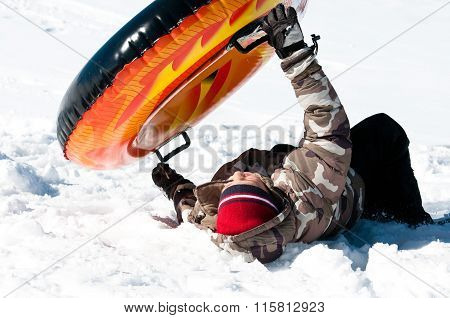 Young Boy Crashing On Tube In The Snow