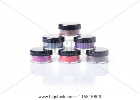 Natural eye shadows in transparent jars, isolated on white background