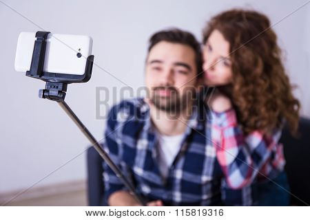 Young Couple Taking Photo With Smart Phone On Selfie Stick