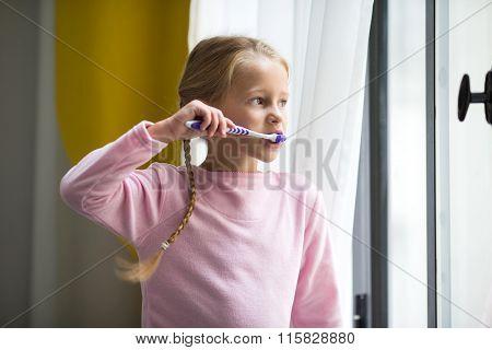 Dental hygiene. Happy little girl brushing her teeth indoor