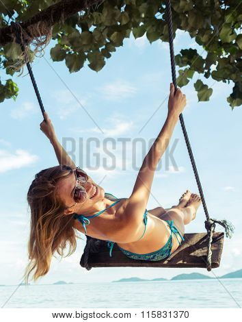 Young happy lady having fun on a swing on a tropical beach