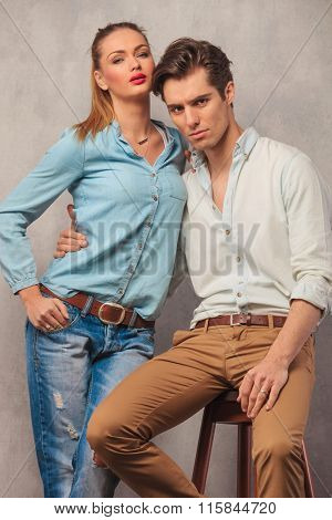 couple posing in studio, the man seated, pulling his girlfriend closer while she stands with hand in pocket