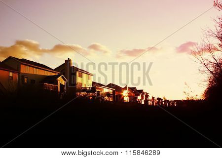 Evening sun setting on a row of suburban houses in a subdivision