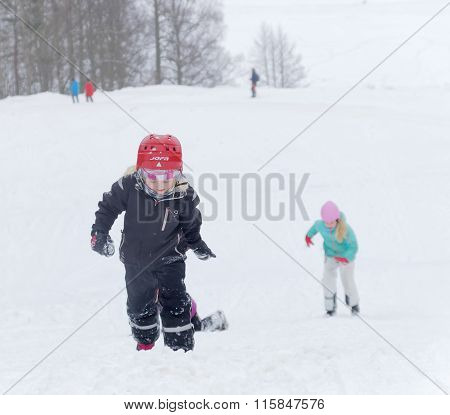STOCKHOLM - JAN 24 2016: Three kids wearing helmets playing in a snowy trees in the background at the Stockholm Ski Marathon event January 24 2016 in Stockholm Sweden