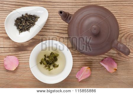Green tea brewed in white tea bowl and tea leaves served with tableware, top view on rustic wooden table decorated rose petals poster