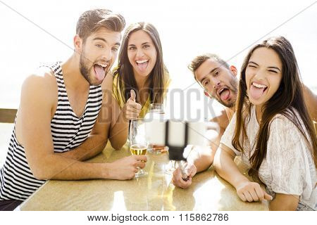 Group of friends at the beach bar and making a selfie