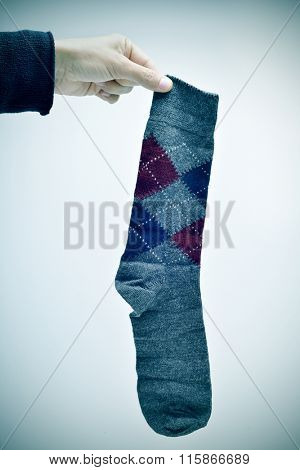 closeup of a young man holding a used argyle patterned sock, with a dramatic vignette added
