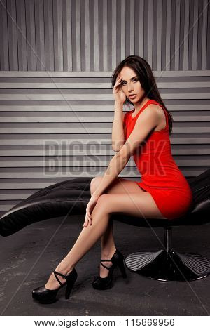 Sexual Brunette In Red Dress Sitting On Black Chair