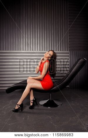 Hot Erotic Woman In Red Dress Sitting On Leather Chair