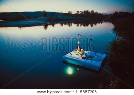 Pretty Woman Is Laying On The Floating Bed With A Book And Toy