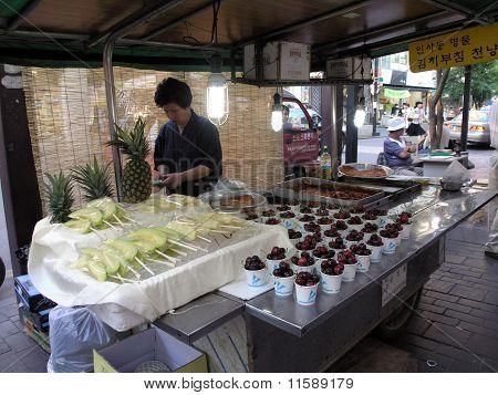 Lady Prepares Food At Food Stand On Sidewalk