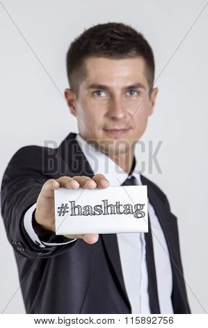 # Hashtag - Young Businessman Holding A White Card With Text