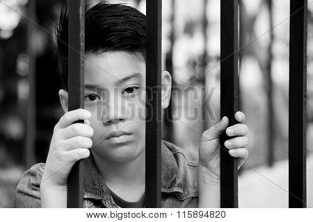 Asian Boy Behind Iron Bars