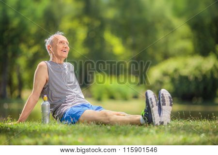 Active senior man in sportswear sitting in park and listening to music on headphones shot with tilt and shift lens