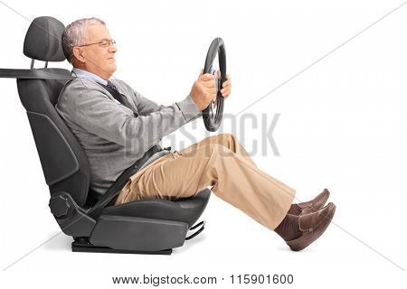 Profile shot of a senior gentleman holding a steering wheel and pretending to drive isolated on white background