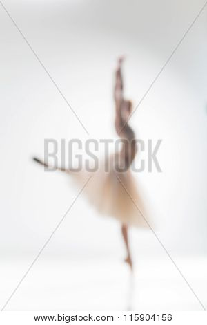 Blurred silhouette of ballerina on white background