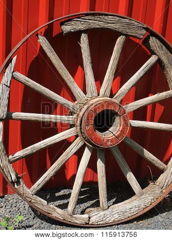 Old Wooden Wagon Wheel Leaning Against A Red Wall