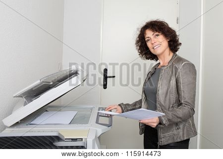 Side View Of A Female Office Worker Using Photocopier In Office