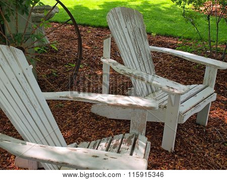 White Wooden Adirondack Chairs Outside In A Yard
