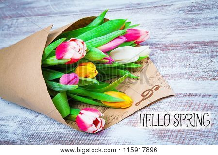 hello spring. tulips in a paper isolated on a wood background