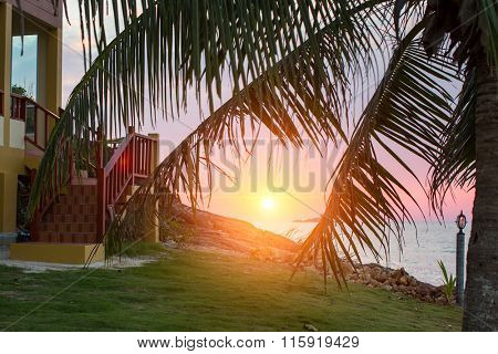 Porch of the house and beautiful sunset on the tropical coast. A rest by the sea.