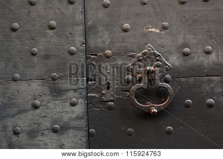Old metal doorknocker on the black painted wooden gate fixed with rivets in Bergamo, Lombardy, Italy.