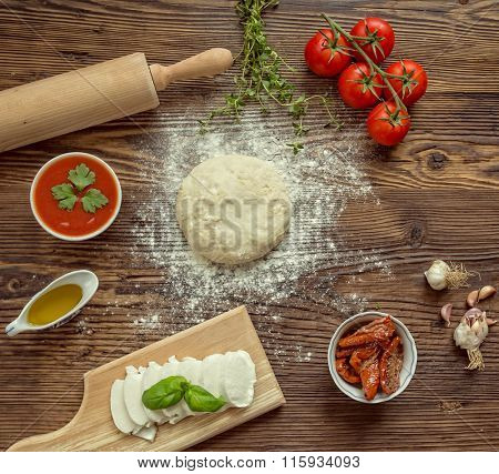 Italian pizza preparation surrounded by ingredients, top view.