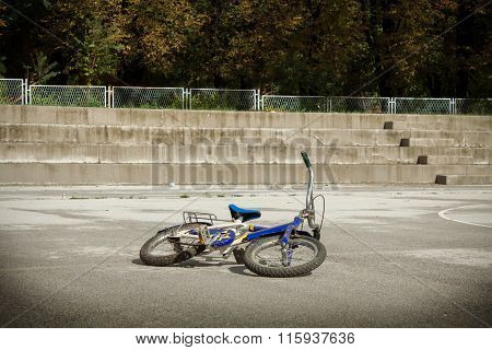 Single Blue Bicycle On Walkway Against A Stone Wall