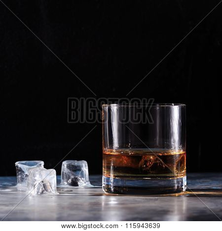 Glass Of Whiskey With Ice On The Table