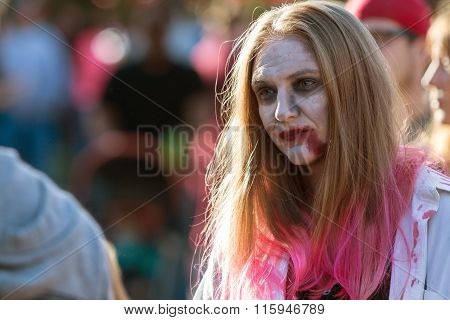 Woman Wearing Zombie Makeup Wanders Through Crowd At Halloween Festival