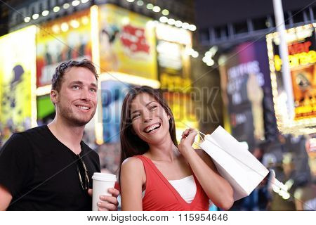 Happy couple shopping fun on New York city travel. Two tourists multiracial group enjoying night on Time Square, USA drinking coffee and walking with shopping bags during summer. American lifestyle.