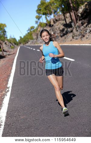 Female road runner training running in outdoor nature. Asian woman jogging fast working out her cardio in blue top and black shorts activewear.