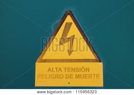 Warning/ danger sign of high voltage with electricity symbol in a yellow triangle with black border. Underneath is Spanish writing 'Alta Tension: Peligro de Muerte' (High Intensity, Danger of Death). Aquamarine background. poster