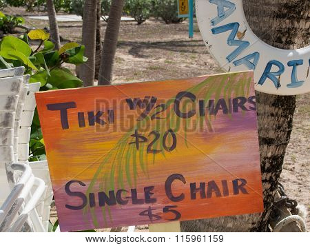 Colorful Sign For A Tiki And Chair On A Beach