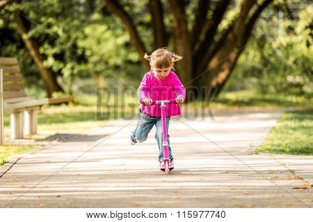 Two years old girl riding her scooter on the park