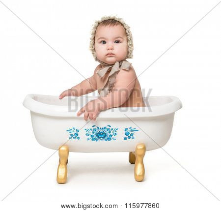little baby in hat siting in a little bath isolated on white background