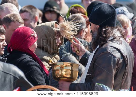 Priest blessing people with holy water. Tyumen
