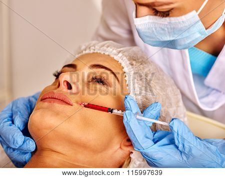 Woman middle-aged in spa salon with doctor. Beauty woman giving anti-ageing injections.