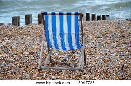 A blue and white striped deckchair on the shingle beach at St.Leonards-on-Sea in East Sussex, England.