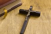 Catholic wooden crucifix and a book bound in leather. poster