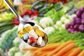 spoon with pills dietary supplements on vegetables background poster