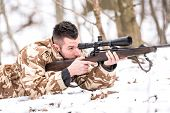 Hunter with a sniper rifle shooting during winter open season poster
