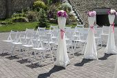 Prior to a wedding ceremony white chairs wait for their guests poster