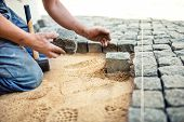 construction worker placing stone tiles in sand for pavement terrace. Worker placing granite cobblestone pavement at local terrace poster