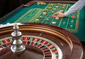 Close up view of Roulette and piles of gambling chips on a green table in casino. Man hand over casino chips on roulette table poster