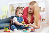 Mother teaches her child to distinguish shape and colur plaing with developmental toys. poster