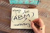 Retro effect and toned image of a woman hand writing a note with a fountain pen on a notebook. Handwritten text ABM ALWAYS BE MARKETING business success concept poster