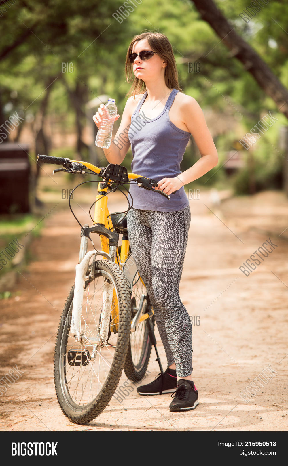 2c431805bf81 A young beautiful girl drinking water from a bottle while holding bicycle  with one hand in