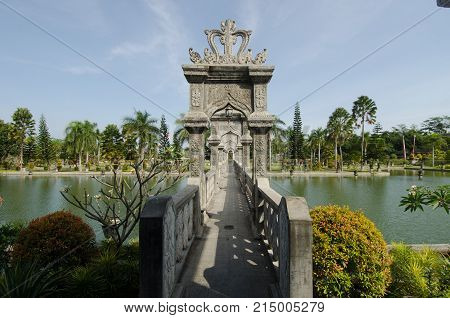 Sculpted stone bridge over artificial pond in Ujun Palace gardens in Bali Indonesia.
